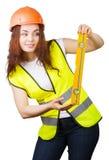 La chica joven el constructor en un casco y un chaleco con el nivel en manos Foto de archivo