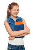 La chica joven elegante en un chaleco y un dril de algodón de los vaqueros pone en cortocircuito con los libros en manos Colegial Imagen de archivo