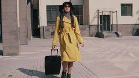 La chica joven elegante en un sombrero amarillo y vidrios del impermeable viene con equipaje almacen de video