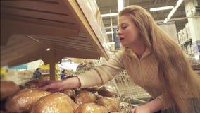 La chica joven elige el pan fresco blanco en vídeo de la cantidad de la acción del supermercado metrajes