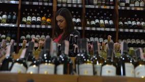 La chica joven elige el vino en la sección del licor en el supermercado almacen de video