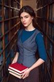 La chica joven elige los libros para leer Imagenes de archivo