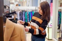 La chica joven, elige nuevas cosas en la tienda El comprador femenino joven hermoso elige cosas tenidas gusto en el boutique Una  foto de archivo