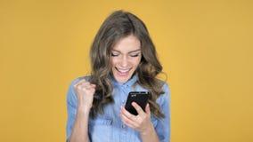La chica joven emocionada para el rato del éxito usando Smartphone aisló en fondo amarillo almacen de video
