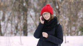 La chica joven emocional con los vidrios y un rojo hicieron punto el sombrero que hablaban en un teléfono celular con un individu metrajes