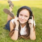 La chica joven en auriculares disfruta de la música que miente en la hierba verde placer Fotos de archivo