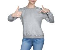 La chica joven en camiseta gris muestra los pulgares para arriba Fondo blanco Fotos de archivo libres de regalías