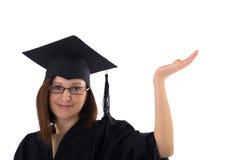 La chica joven en capa del estudiante indica la mano Fotos de archivo libres de regalías