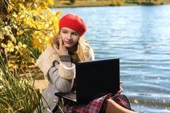La chica joven en casquillo rojo está estudiando en naturaleza con el ordenador portátil imágenes de archivo libres de regalías