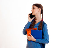La chica joven en chaqueta azul en el teléfono y mantiene los paquetes disponibles Imagen de archivo