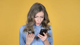 La chica joven en choque mientras que usando Smartphone aisló en fondo amarillo metrajes