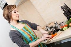 La chica joven en delantal rayado cocina verduras imagen de archivo