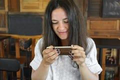 La chica joven en el café, fotografías en la comida del teléfono, una taza de té, café, apelmaza verde Fotos de archivo libres de regalías