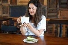 La chica joven en el café, fotografías en la comida del teléfono, una taza de té, café, apelmaza verde Fotos de archivo