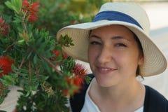La chica joven en el goce del sombrero del árbol rojo floreciente del syringa florece el olor en parque soleado fotografía de archivo