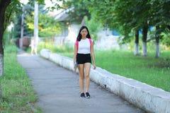 La chica joven en el parque es paso que camina Imagenes de archivo