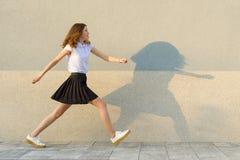 La chica joven en el perfil, paseos a lo largo de la pared gris, prisa, es atrasada, toma medidas grandes Al aire libre, copie el foto de archivo libre de regalías