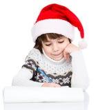 La chica joven en el sombrero de Papá Noel escribe la letra a Papá Noel Fotos de archivo