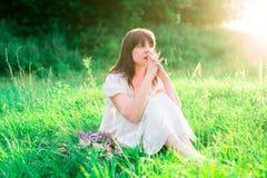 La chica joven en el vestido blanco que se sienta en el medio del campo y refleja Tristeza, soledad, duda Foto de archivo libre de regalías