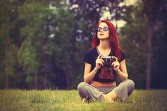La chica joven en estilo del indie viste con la cámara retra Imágenes de archivo libres de regalías