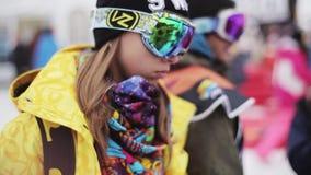 La chica joven en gafas de sol del esquí camina adentro acampa en estación de esquí Gente holidays almacen de metraje de vídeo