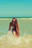 La chica joven en la agua de mar salpica y sonrisa Imagen de archivo