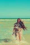 La chica joven en la agua de mar salpica y sonrisa Fotografía de archivo libre de regalías