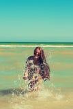 La chica joven en la agua de mar salpica y sonrisa Foto de archivo