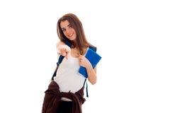 La chica joven en la camisa blanca y con una mochila en hombro estira el brazo delantero y la sonrisa Imagen de archivo