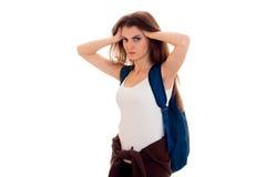 La chica joven en la camisa blanca y con una mochila en hombro guarda la cabeza de las manos Imágenes de archivo libres de regalías