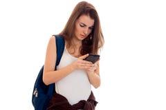 La chica joven en la camisa blanca y con una mochila en su hombro sostiene el teléfono móvil Fotos de archivo