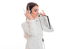 La chica joven en la camisa y los auriculares blancos con el micrófono se coloca de torneado de lado y levantó sus manos para dir Foto de archivo libre de regalías