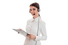 La chica joven en la camisa y los auriculares blancos con el micrófono se coloca de torneado de lado y que sostiene una tableta Foto de archivo libre de regalías