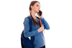 La chica joven en la chaqueta azul que sostenía una cartera y dijo por el teléfono móvil Fotos de archivo