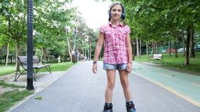 La chica joven en las cuchillas del rodillo patina en el parque almacen de metraje de vídeo