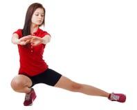 La chica joven en pantalones cortos cortos y una camisa de deportes realiza posiciones en cuclillas Aislado Fotos de archivo libres de regalías