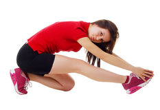 La chica joven en pantalones cortos cortos y una camisa de deportes realiza posiciones en cuclillas Aislado Foto de archivo libre de regalías