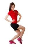 La chica joven en pantalones cortos cortos y una camisa de deportes realiza posiciones en cuclillas Aislado Imagenes de archivo