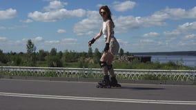 La chica joven en pantalones cortos y tops patina en pcteres de ruedas Imagen de archivo libre de regalías