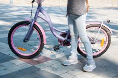 La chica joven en pantalones del dril de algodón se coloca cerca de la bici que lo sostiene imagen de archivo