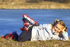 La chica joven en pcteres de ruedas pone en la tierra Foto de archivo