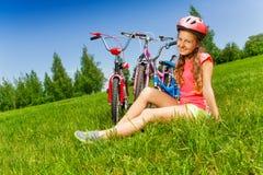 La chica joven en rojo se sienta en un prado Fotografía de archivo libre de regalías