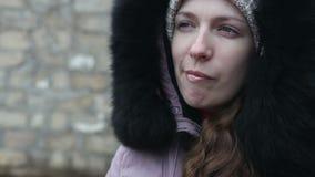 La chica joven en ropa del invierno mastica el bolo alimenticio metrajes