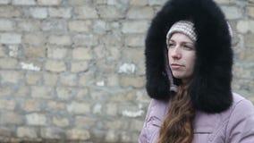 La chica joven en ropa del invierno mastica el bolo alimenticio almacen de metraje de vídeo