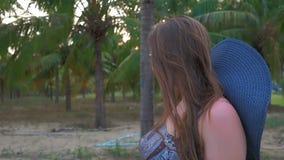 La chica joven en sombrero y vidrios azules va contra el fondo de las palmas de coco tropicales Ciérrese encima de tiro Cámara le metrajes