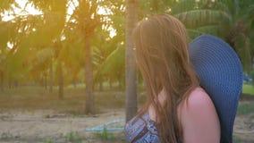 La chica joven en sombrero y vidrios azules va contra el fondo de las palmas de coco tropicales Ciérrese encima de tiro Cámara le almacen de metraje de vídeo