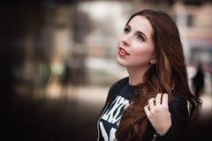 La chica joven en sonrisas y sueños de una chaqueta de cuero Imágenes de archivo libres de regalías