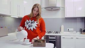 La chica joven en suéter rojo hace té en la cocina metrajes