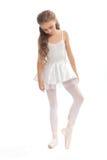 La chica joven en su danza viste alcanzar abajo para tocar su pie Imágenes de archivo libres de regalías