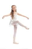 La chica joven en su danza viste alcanzar abajo para tocar su pie Fotografía de archivo libre de regalías